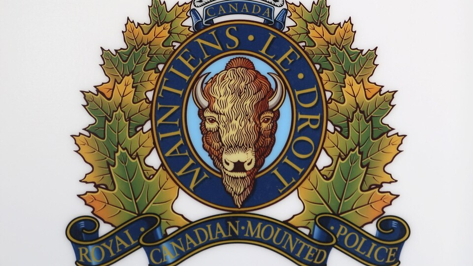 Armoiries de la Gendarmerie royale du Canada montrant un buffle couronné et ceinturé de feuilles d'érable. L'écusson porte la devise du corps policier : « Maintiens le droit ».