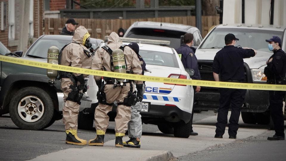 Des policiers portant des combinaison et des masques discutent entre eux.