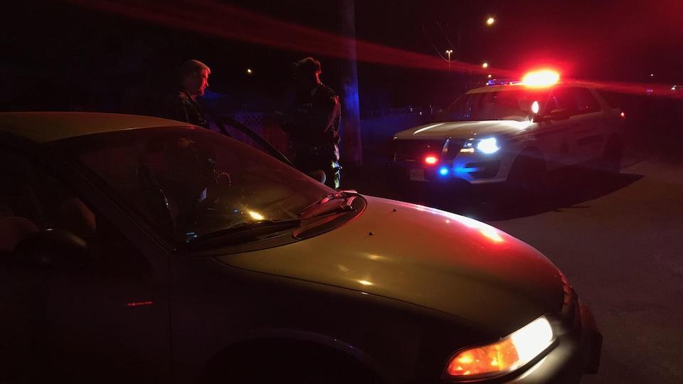 Deux voitures de police, une identifiée de la GRC et l'autre banalisée sur une scène de crime à Surrey. Deux policiers parlent à côté des voitures.
