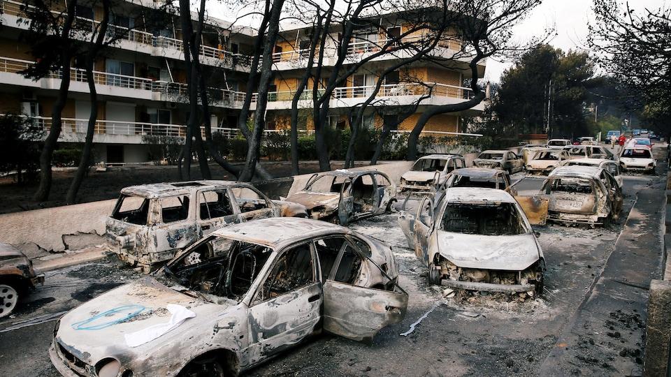 Des carcasses de voitures carbonisées dans une rue.