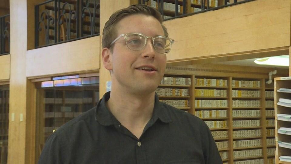 Joshua Green en entrevue dans une salle pleine de documents archivés