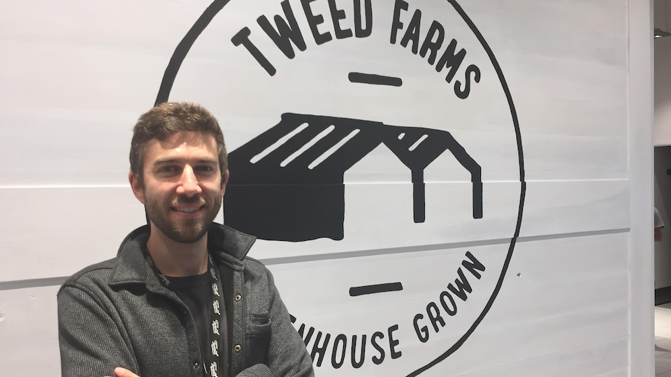 Adam Greenblatt pose devant un mur arborant en gros le logo de « Tweed Farms.