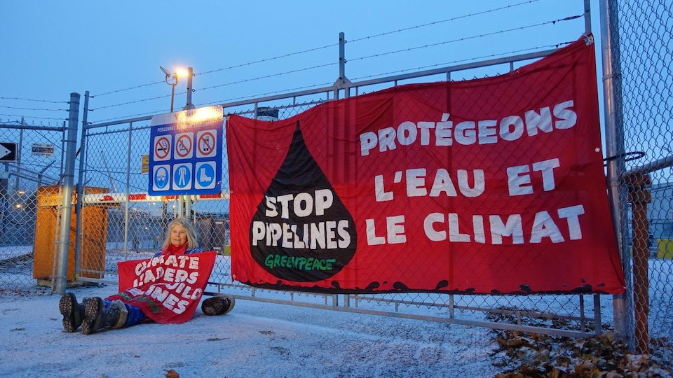 Une personne est assise contre une clôture recouverte d'une affiche et près d'une autre grande affiche accrochée à la clôture ou il est écrit : « Protégeons l'eau et le climat : stop pipelines ».