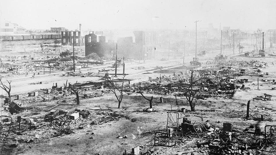 Des restes de bâtiments en cendres.