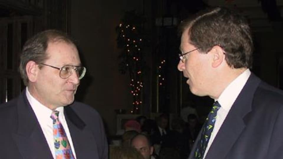 Deux hommes d'affaires debout en train de discuter.