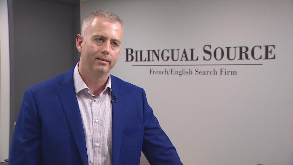 Un homme dans un costume bleu foncé parle à la caméra devant l'entrée de son entreprise, Source Bilingue.