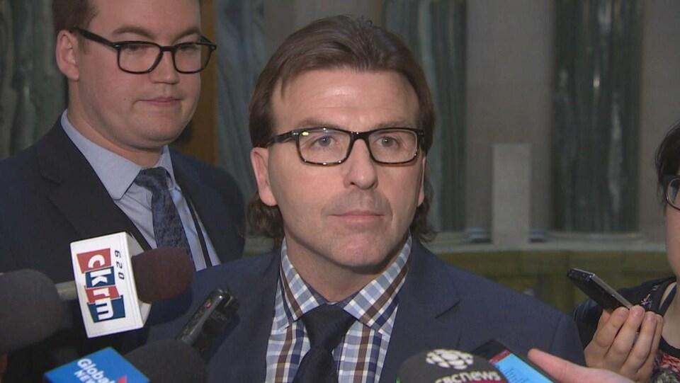 Le ministre Greg Ottenbreit parle aux journalistes dans le hall de l'Assemblée législative à Regina.