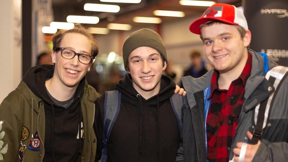 Trois jeunes hommes sourient pour la photo.