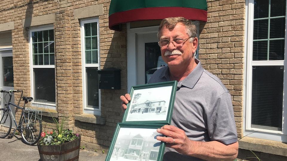 Le maire de Champlain, Gregory Martin, tient fièrement des photos de l'hôtel de ville à l'époque où s'y trouvait le concessionnaire Tremblay Chevrolet.