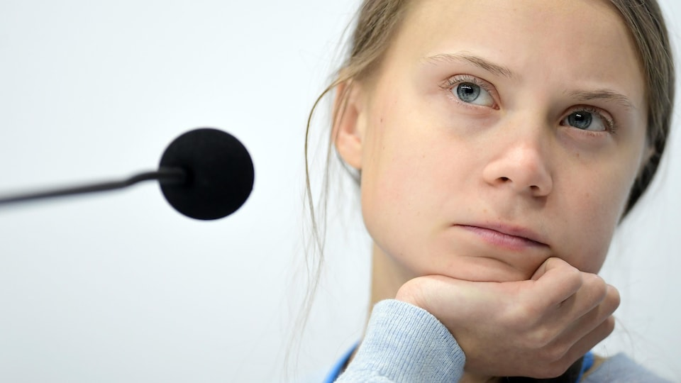 Plan rapproché de Greta Thunberg, qui affiche un air perplexe.