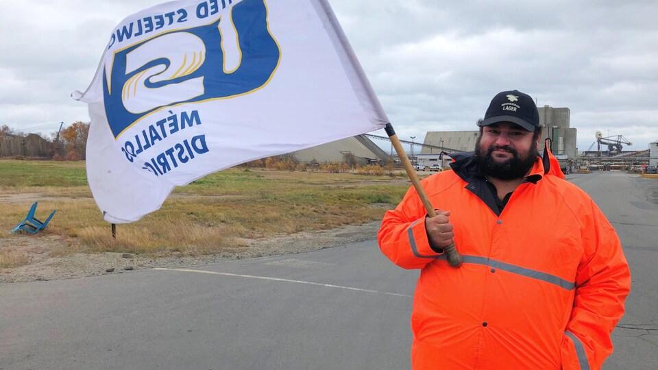 Marcel Doucet, un employé de la Fonderie Brunswick en grève, tenant un drapeau de son syndicat devant l'usine.