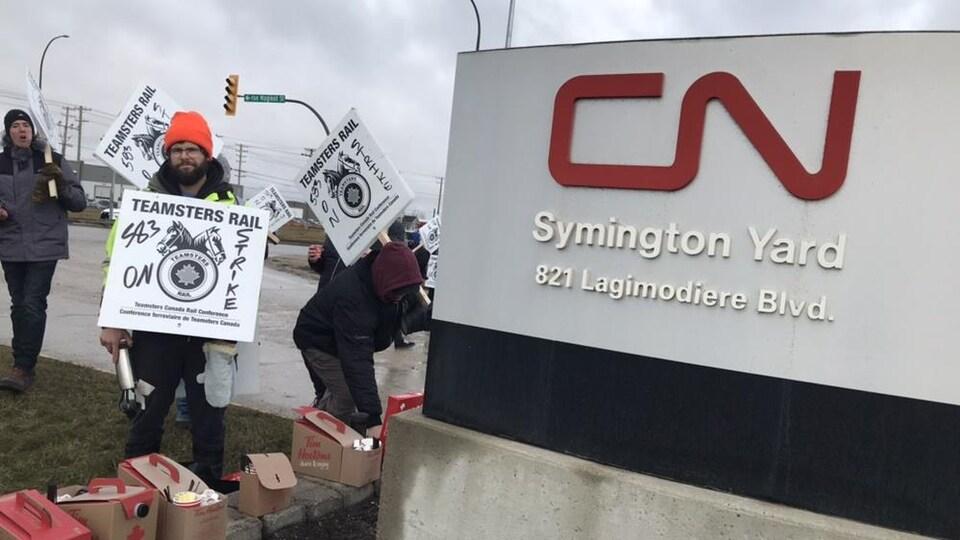 Un panneau CN à côté de plusieurs grévistes tenant des affiches.
