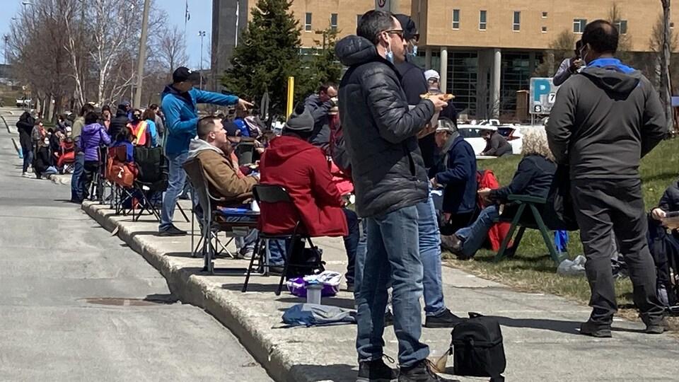 Des enseignants debout et assis sur le trottoir devant le Cégep.