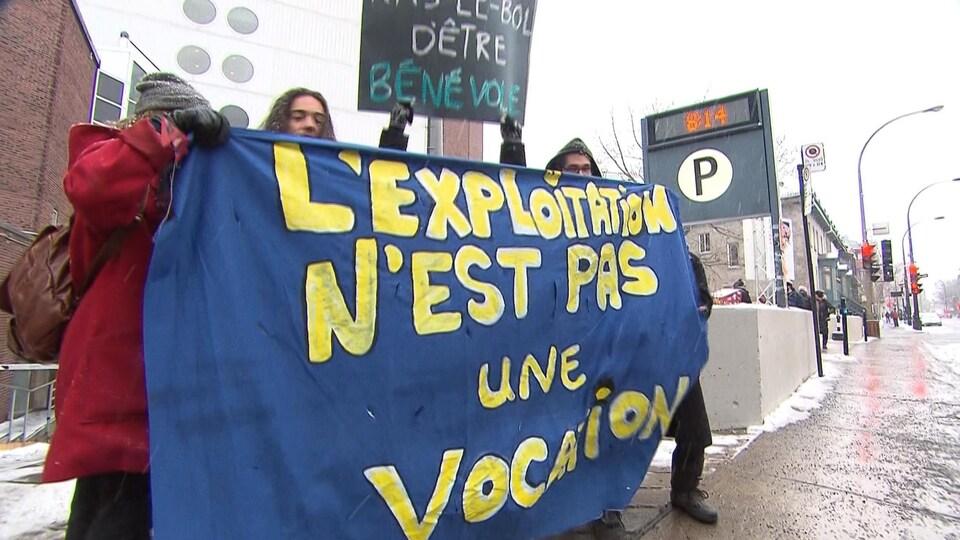 Des étudiants brandissent une affiche où on peut lire : «L'exploitation n'est pas une vocation».