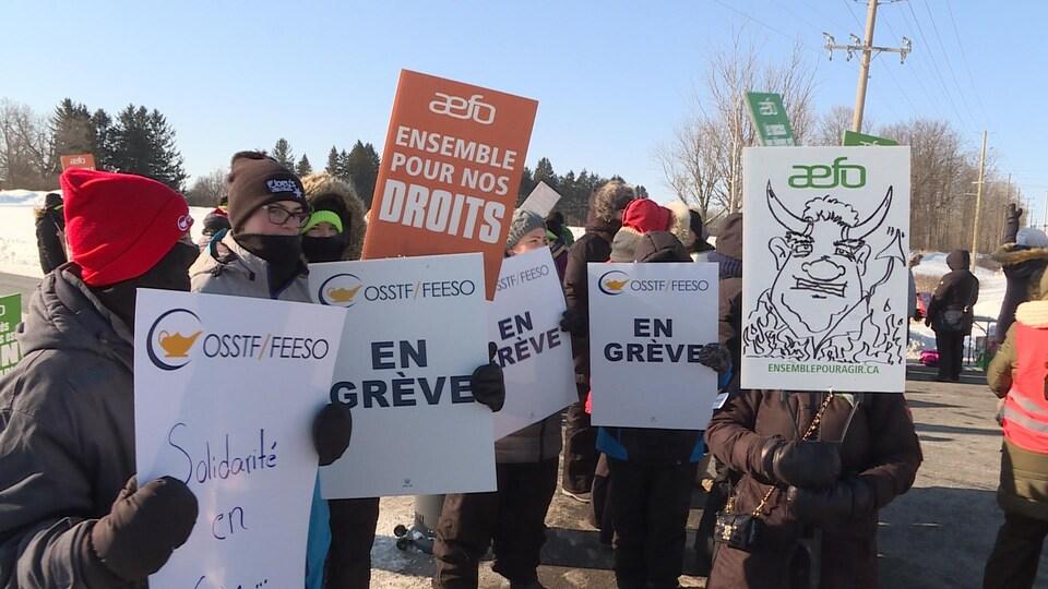 Des manifestants dehors en hiver avec des pancartes dénonçant les compressions en éducation.