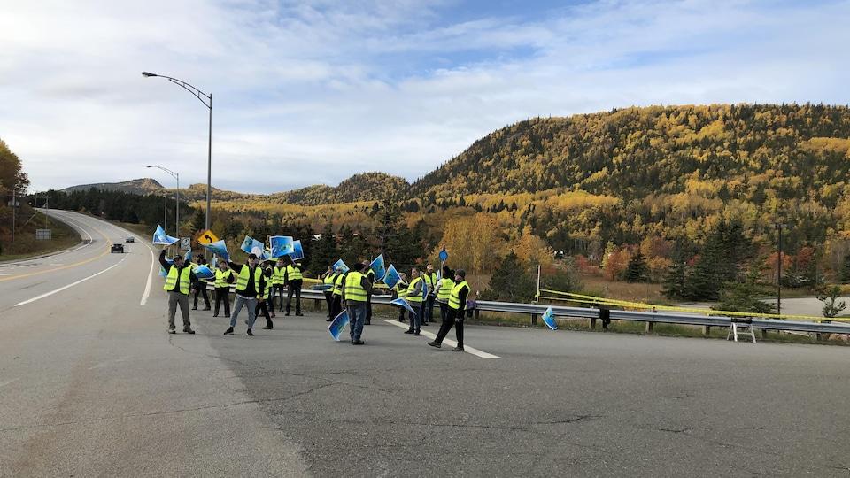 Vêtus de dossards, des employés brandissent des pancartes en bordure d'une route.
