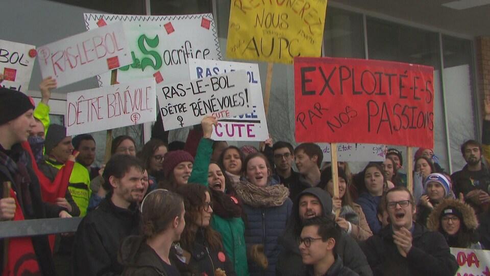 Des étudiants tiennent des pancartes.