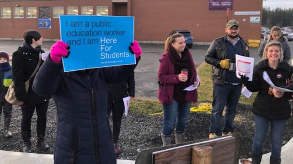 Des gens qui distribuent des feuillets d'information et qui tiennent des pancartes.