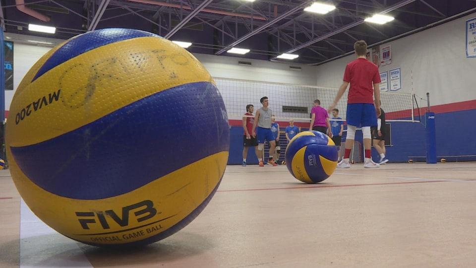 Un ballon à l'avant-plan, devant un entraînement de volleyball.