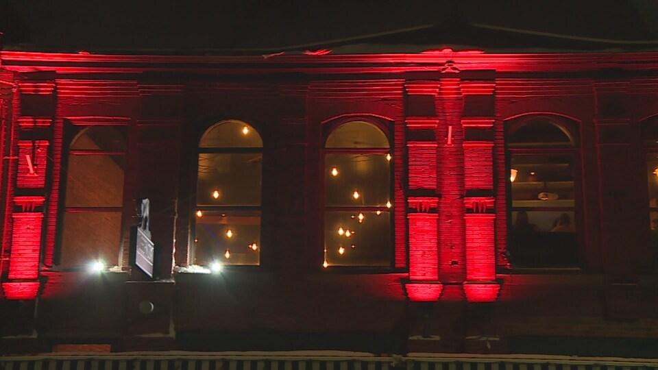 Un immeuble éclairé en rouge.