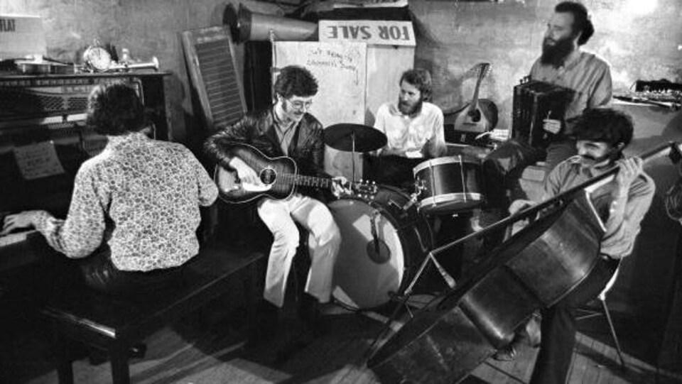 Richard Manuel, Robbie Robertson, Levon Helm, Garth Hudson et Rick Danko jouent dans un sous-sol, au milieu de meubles entreposés.