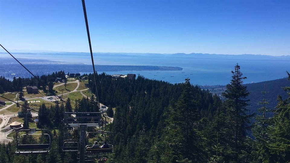 En avant-plan, les chaises d'un téléphérique, au-dessus d'un flanc de montagne boisé avec en arrière-plan une grande étendue d'eau.