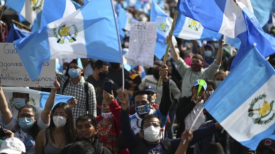 Une foule brandit des drapeaux du Guatemala.