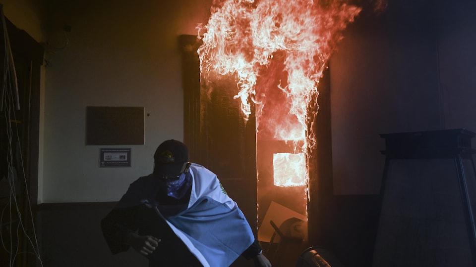 Un homme qui porte le drapeau du Guatemala en guise de cape se déplace au pas de course tandis que des flammes sortent d'une porte derrière lui.