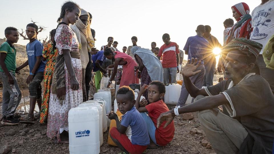 Des réfugiés qui se servent de l'eau dans des bidons de l'UNICEF.