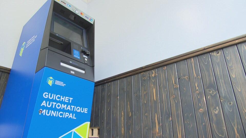 Un guichet automatique municipal installé dans une petite pièce.