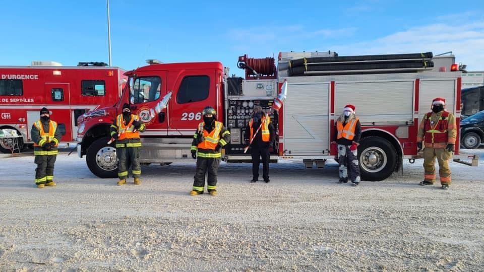 Des pompiers devant leur camion. Ils se tiennent à bonne distance l'un de l'autre.