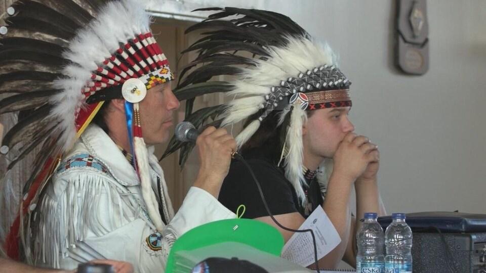 Guillaume Carle, portant un couvre-chef autochtone, parle dans un micro.