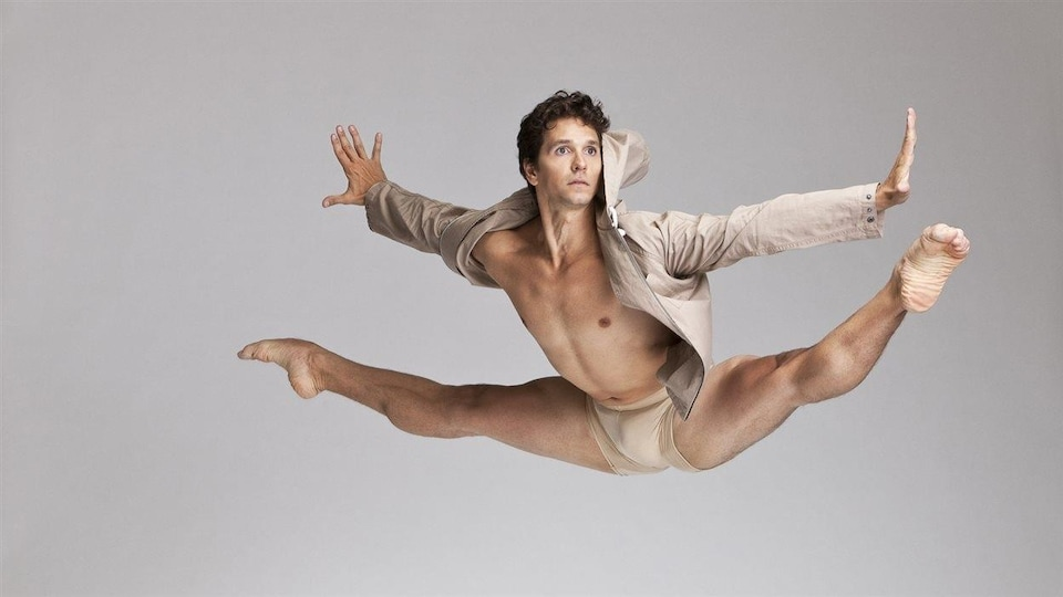 Le danseur Guillaume Côté est posé alors qu'il fait le grand écart dans les airs. On comprend qu'il a jumelé un saut et la figure du grand écart. L'artiste est vêtu d'une culotte et d'un manteau court beiges.