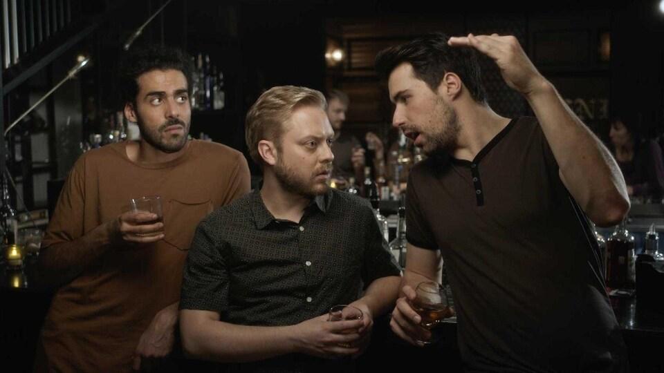 Adib Alkhalidey, Guillaume Lambert et Philippe-Audrey Larrue St-Jacques, accoudés à un bar, en train de discuter, dans une scène de la série «Like-moi».