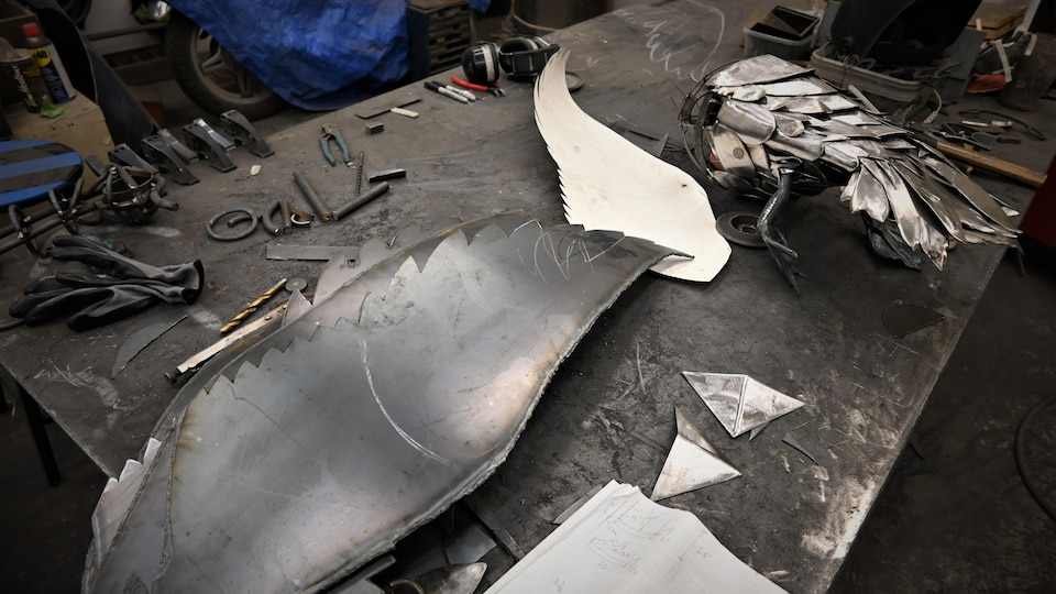 Sur une table de travail, la forme des ailes des canards a été découpée à partir d'un gabarit en papier sur une feuille de métal.
