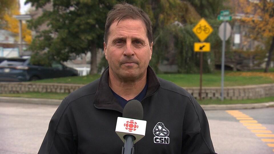 Le président de la CSN Côte-Nord, Guillaume Tremblay devant la caméra et un micro de Radio-Canada.