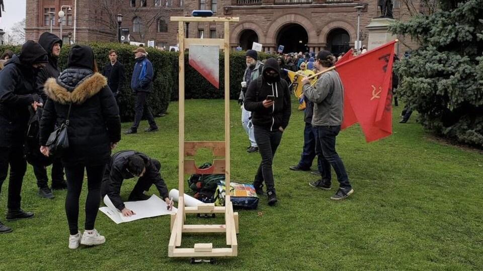 Des manifestants sur la pelouse devant l'Assemblée législative ontarienne avec une construction qui fait penser à une guillotine.