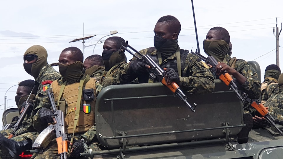 Plusieurs militaires armés dans un véhicule militaire.