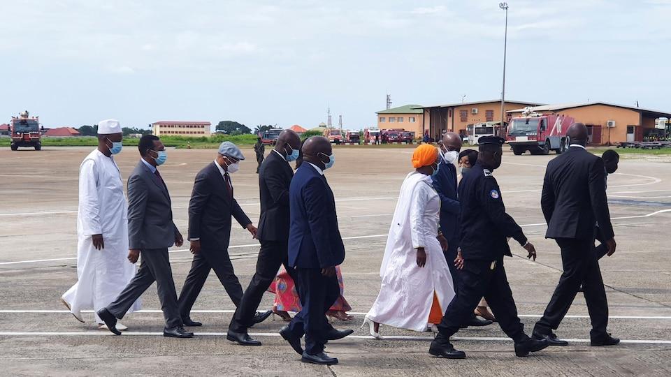 Plusieurs personnes marchent sur le tarmac d'un aéroport.