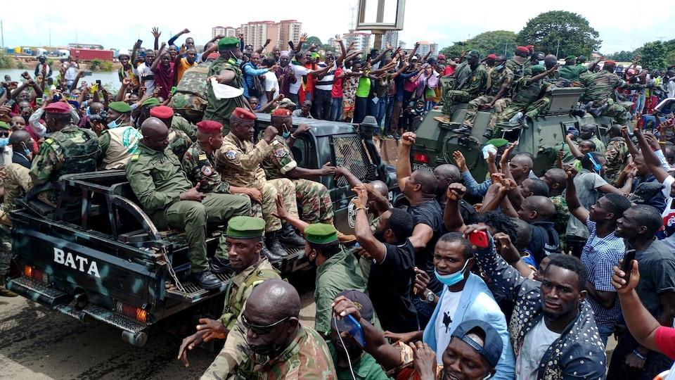 Des militaires passent à travers une foule en liesse.