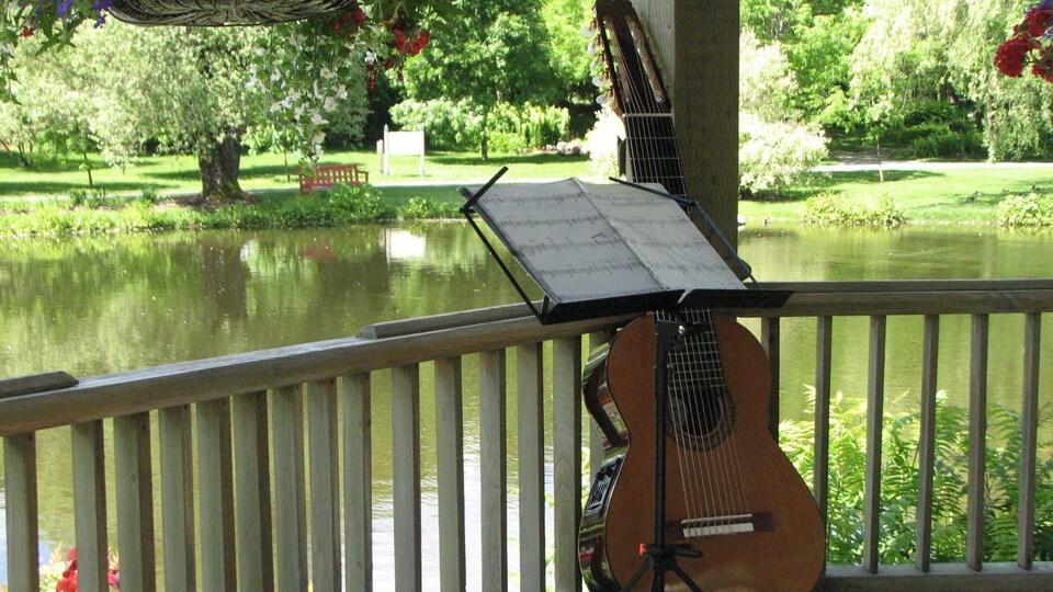 Guitare appuyée sur un lutrin sur lequel est posée une partition musicale.