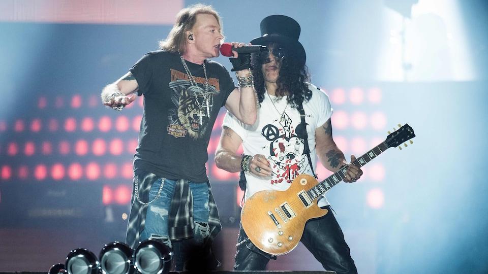 Le chanteur Axl Rose et le guitariste Slash côte à côte sur scène lors d'un concert.