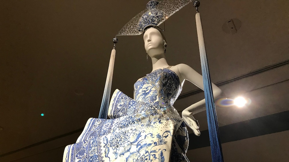Une robe bleue et blanche en forme d'éventail sur une mannequin dans un musée.