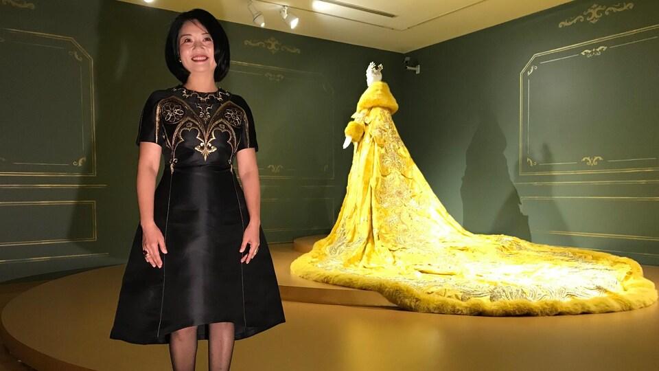 Une dame devant une robe jaune avec une longue traîne.