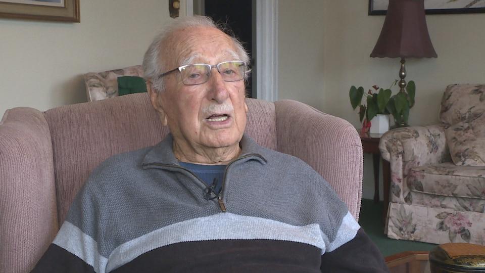 Gus Etchegary relate ses souvenirs, assis dans son salon.
