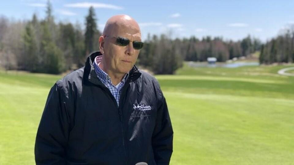 Un homme répond aux questions d'une journaliste sur un terrain de golf à Gatineau.