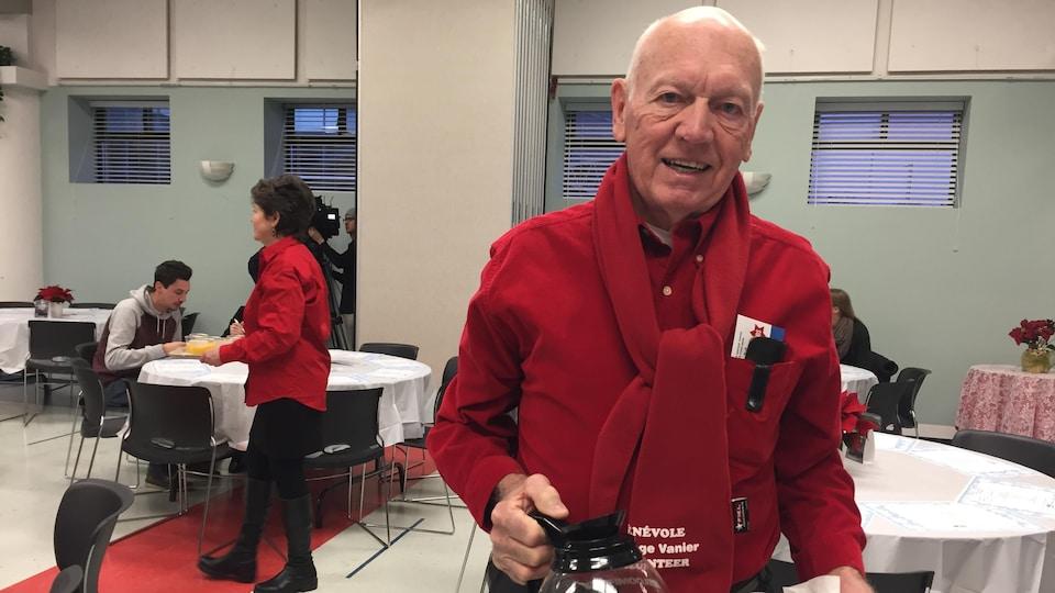 Monsieur Cousineau  regarde la caméra avec une carafe de café dans la main.