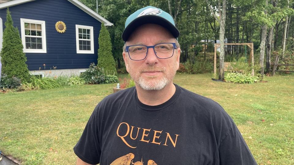 Portrait d'un homme avec des lunettes et une casquette.
