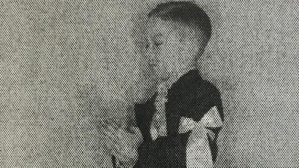 Enfant qui porte un brassard. Il joint les mains et ferme les yeux