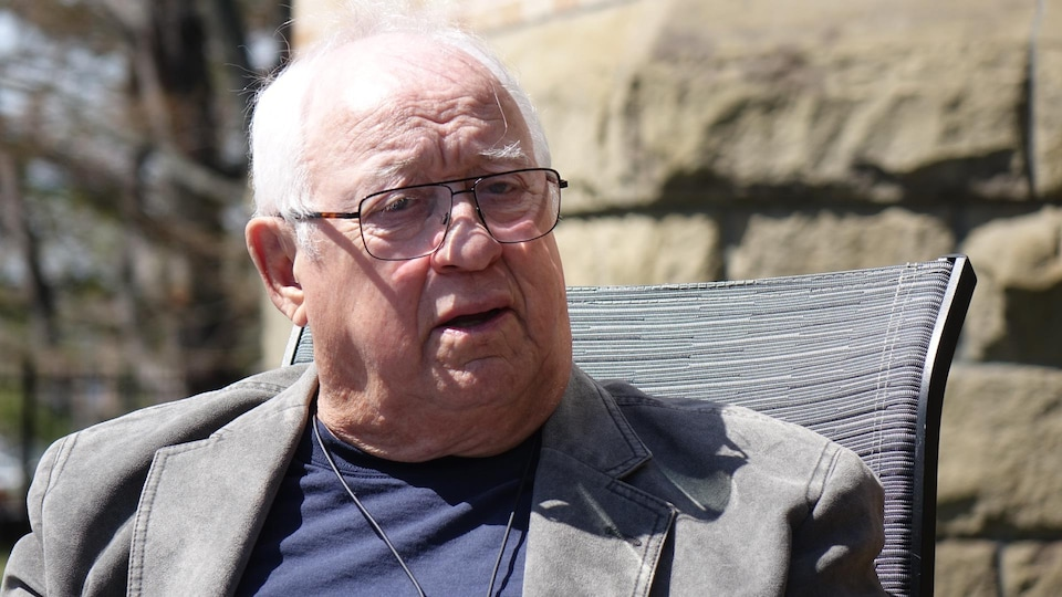 Guy Lagacé est assis à l'extérieur, lors d'une entrevue.